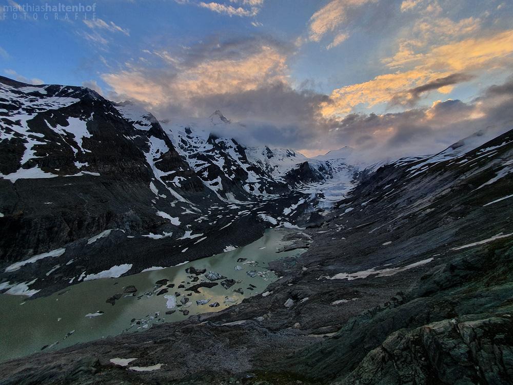 Sonnenuntergang über den Resten des Gletschers Pasterze, mitte-links in den Wolken die Spitze des Großglockners