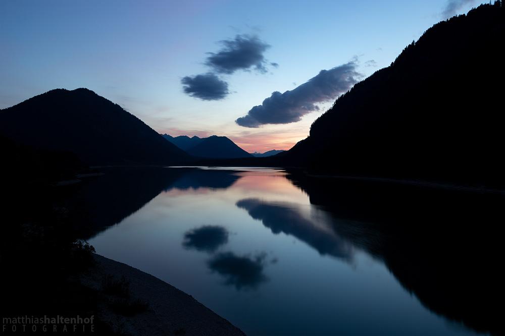 Das letzte Licht des Sonnenuntergangs über dem Sylvensteinsee.