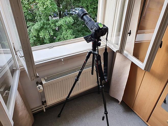 Kamera mit Stativ vor dem geöffneten Fenster (nachgestellt)