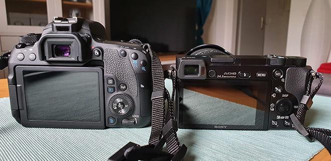 Spiegelreflexkamera und Systemkamera von hinten - links DSLR (Canon EOS 77D), rechts DSLM (Sony Alpha 6000)